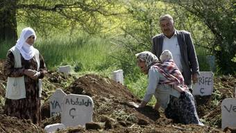 Familienangehörige trauern bei den Gräbern um die Verstorbenen (Archiv)