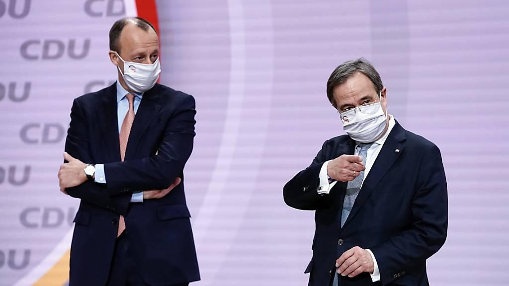 Der unterlegene Friedrich Merz (l) steht neben Abstimmunssieger Armin Laschet beim digitalen CDU-Bundesparteitag auf dem Podium. Foto: Michael Kappeler/dpa