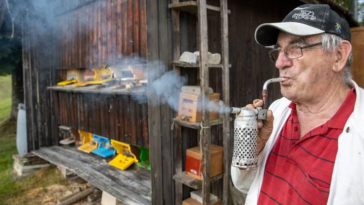 Remy Horisberger beruhigt die Bienen mit Rauch aus einer Bienenpfeife.