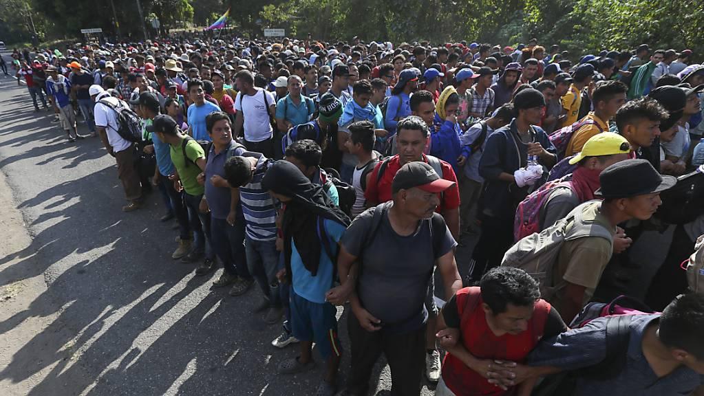 Von mexikanischen Nationalgardisten aufgehaltene Migranten bilden in der Nähe der mexikanisch-guatemaltekischen Grenze eine Menschenkette.