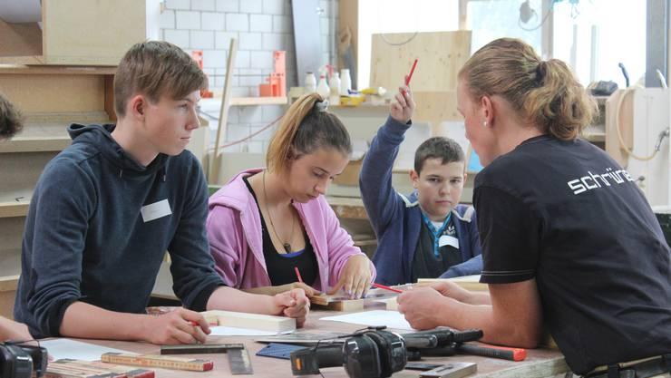 Alexandra Stutz (rechts) erklärt den Schülern, wie sie die beiden Holzstücke zusammensetzen müssen.