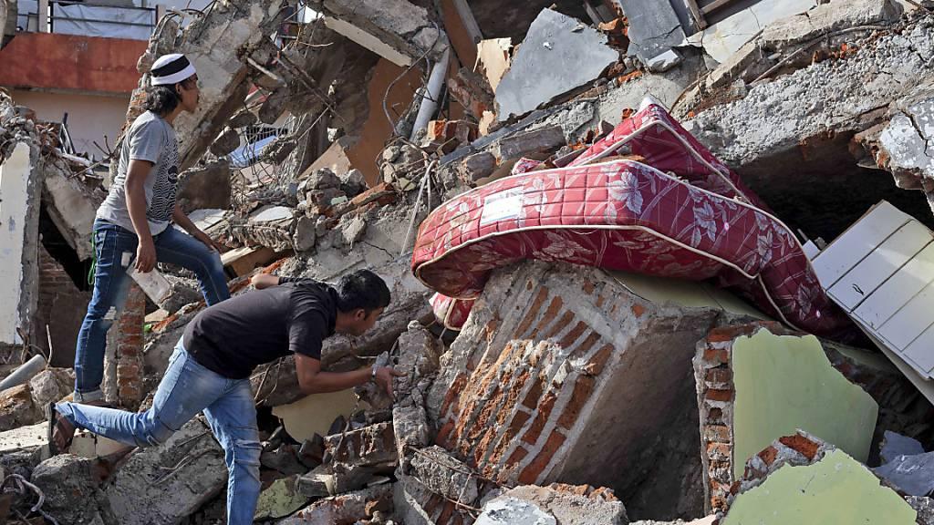 Anwohner inspizieren ein Gebäude, das bei einem Erdbeben eingestürzt ist. Foto: Yusuf Wahil/AP/dpa