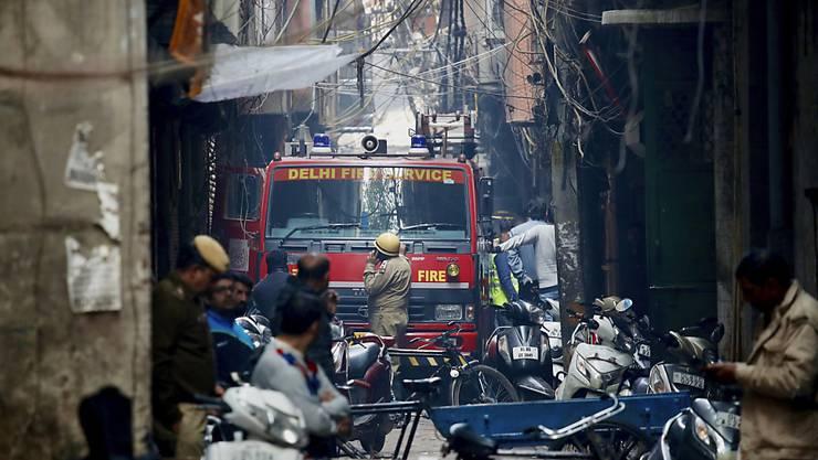 Für ein Feuerwehrauto, das in der Nähe des Brandortes steht, gab es in den engen Gassen fast kein Durchkommen mehr. Beim Grossbrand in einer indischen Fabrik starben über 40 Menschen. (AP Photo/Manish Swarup)