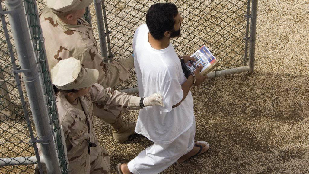Ein Gefangener wird im Gefangenenlager von Guantanamo von US-Armeeangehörigen eskortiert. (Archivbild)