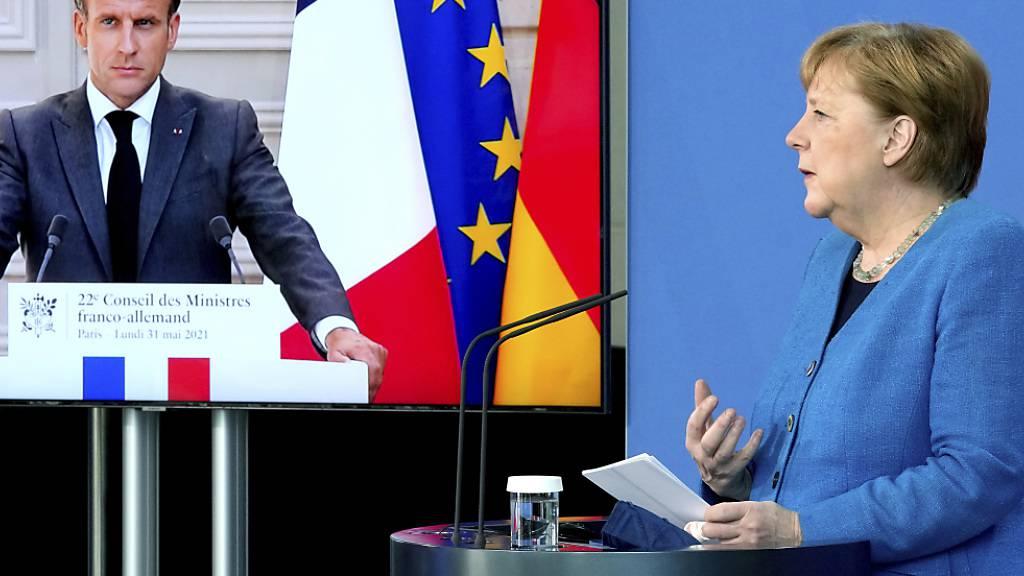 Frankreichs Präsident Emmanuel Macron ist bei einer gemeinsamen Pressekonferenz mit Bundeskanzlerin Angela Merkel auf einem Bildschirm zu sehen. Foto: Michael Sohn/POOL AP/dpa