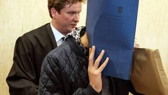 Der Angeklagte verhüllt sein Gesicht, als er das Gericht mit seinem Anwalt betritt.