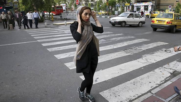 Eine iranische Frau richtet ihr lose getragenes Kopftuch - eine andere nahm ihr Kopftuch ganz ab und wurde nun zu einer Haftstrafe verurteilt. (Archiv)
