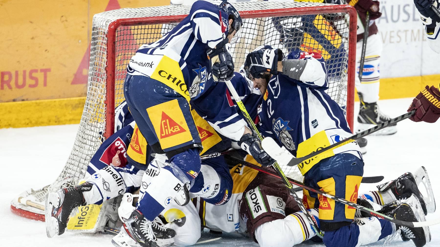 Zugs Nico Gross, Servettes Eric Fehr, am Boden, und Zugs Yannick Zehnder, von links, im ersten Eishockey Playoff-Finalspiel der National League zwischen dem EV Zug und Geneve-Servette HC am Montag, 3. Mai 2021, in der Bossard Arena in Zug.