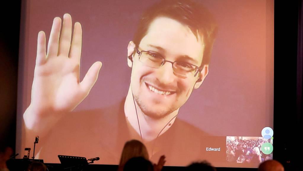 ARCHIV - Der NSA-Enthüller Edward Snowden winkt während einer Videoschalte dem Publikum zu. Der US-Whistleblower Edward Snowden ist Vater geworden. Foto: Wolfgang Kumm/dpa