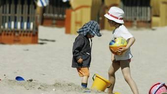 Zwei Kinder spielen am Strand mit einem aufblasbaren Ball. (Symbolbild)