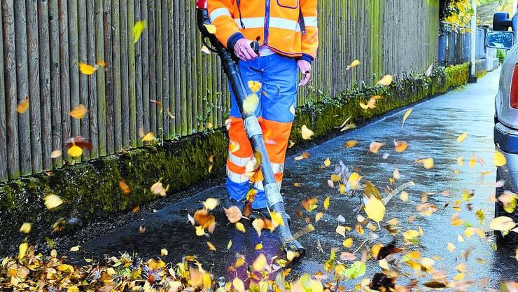 Laubbläser: Rolf Hängärtner wirbelt die Blätter vom Trottoir auf die Strasse. (Bild: Oliver Menge)