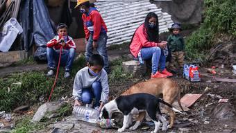ARCHIV - Ein Junge und zwei Hunde in einem Elendsviertel im kolumbianischen Bogotá. Foto: Camila Diaz/colprensa/dpa