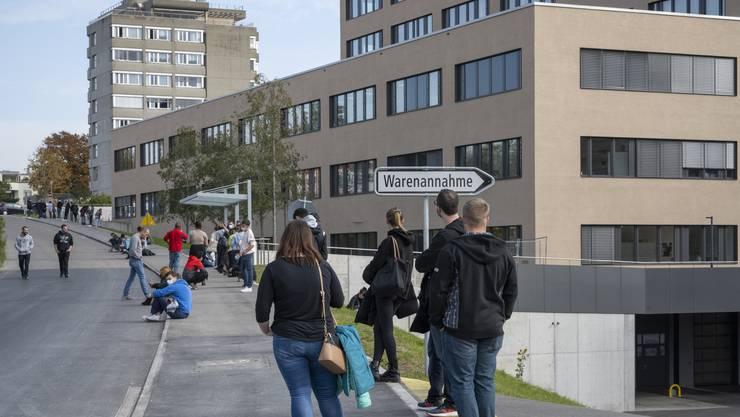 Täglich sind es mehr: Leute warten vor dem Testzentrum im Spital Limmattal auf den Covid-19-Abstrich. Sie brauchen ihre Maske und Geduld.