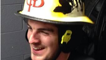 Reto Berra mit dem Feuerwehrhelm, der den besten Flames-Spieler auszeichnet.