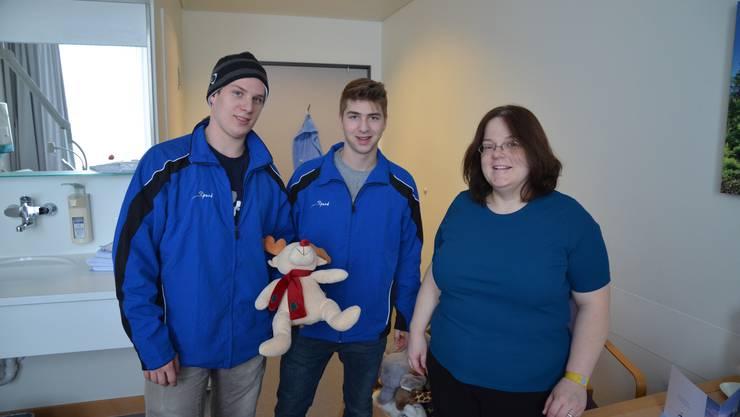 Ursula Tobler aus Rudolfstetten zusammen mit den EVZ-Spielern Dominik Lammer und Lino Martschini; das Baby Victoria verschlief die Übergabe des Stofftieres.