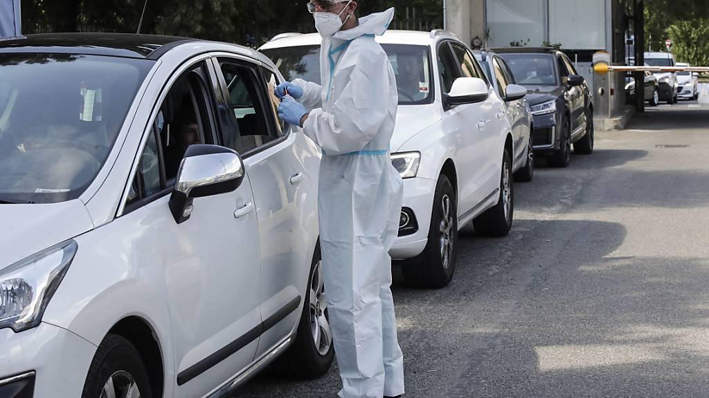 Ein medizinischer Mitarbeiter im Schutzanzug entnimmt an einer Drive-Thru-Station vor dem San Carlo Borromeo Krankenhaus Abstriche für Corona-Tests. Foto: Luca Bruno/AP/dpa