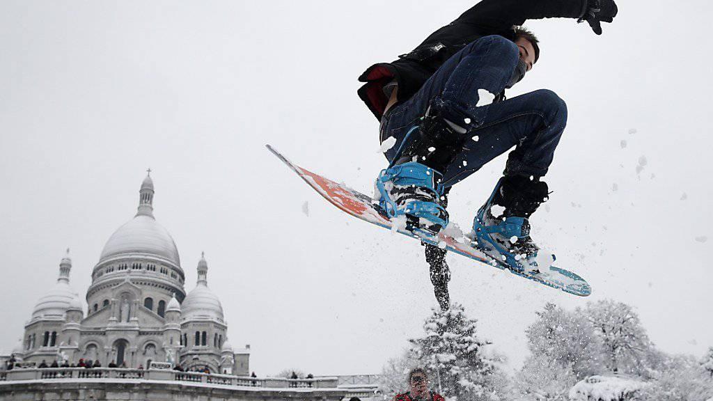 Snowboarden vor der Sacré-Coeur Basilika: Dieser Mann geniesst den Schnee in Paris offenbar.