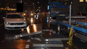 Betonelemente kippen in Pratteln von einem Lastwagen-Anhänger und beschädigen ein Auto.