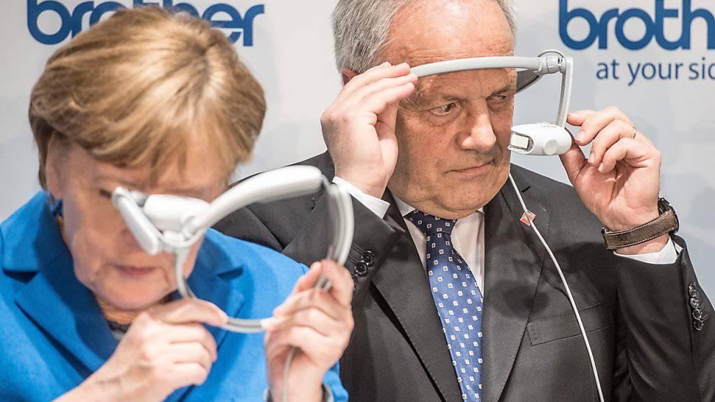 Angela Merkel und  Johann Schneider-Ammann schauen an der CeBIT durch Augmented-Reality-Brillen.