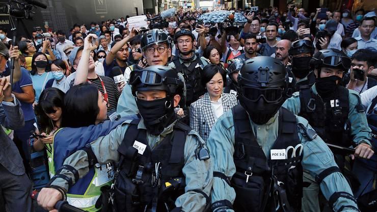Eine pekingtreue Politikerin wird nach der Wahl von der Polizei durch Hongkong eskortiert. (Bild: Fazry Ismail/EPA, 25. November 2019))