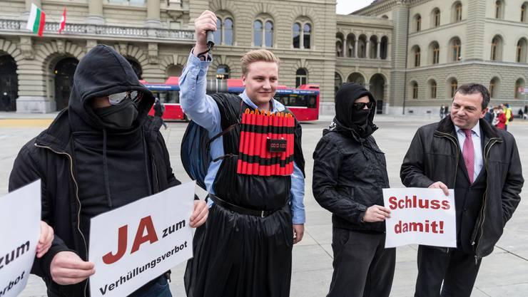 SVP-Nationalrat Walter Wobmann (rechts) posiert mit Statisten, die sich als burkatragende Terroristen und Vermummte inszenieren.