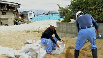 """Japan bereitet sich auf den Taifun """"Cimaron"""" vor: Arbeiter füllen Sandsäcke und errichten Dämme."""