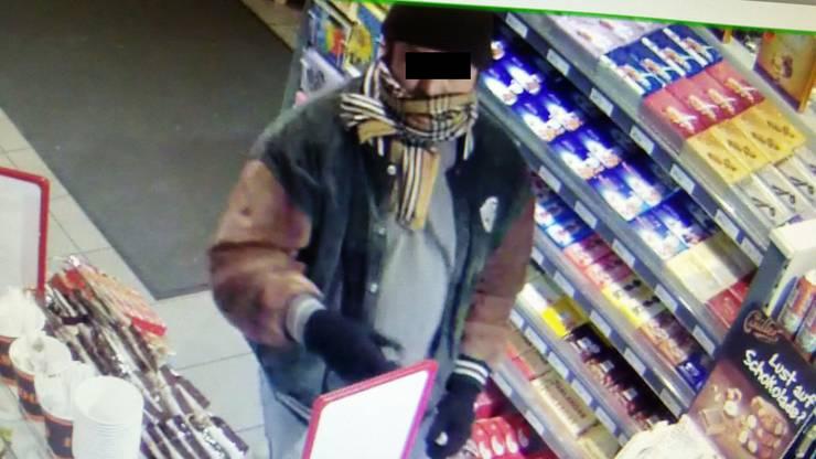 Der mit einem Schal und Kappe maskierte Täter.