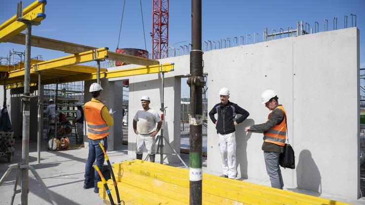 Zwei Kontrolleure arbeiten auf der Baustelle in Wettingen die Checkliste des Bundes zur Einhaltung der Hygienemassnahmen auf Baustellen ab.
