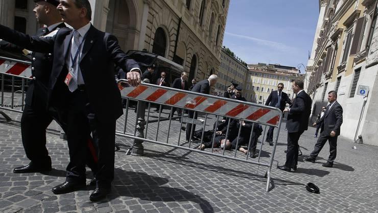 Ein verletzter Carabiniere liegt am Boden. Ein Mann hat zuvor vor dem Sitz des Ministerpäsidenten mehrere Schüsse abgegeben.