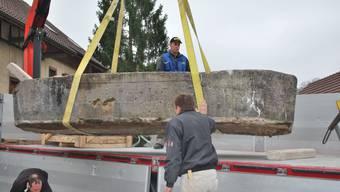 Erich Fringeli verlädt mit dem Kran den Brunnentrog, Adrian Weber richtet den Trog von unten her aus.