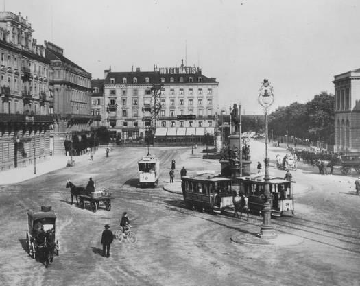 war in Zürich ab 1882 unterwegs. Ab 1894 fuhren auch elektrische Trams durch die Stadt. Das Foto aus dem Zeitraum 1899/1900 zeigt beide Tramarten auf dem Bahnhofplatz, nebst Fussgängern, Velofahrern und Pferdekutschen, die den Platz kreuz und quer nutzen. Etwas fehlt noch: das Auto.