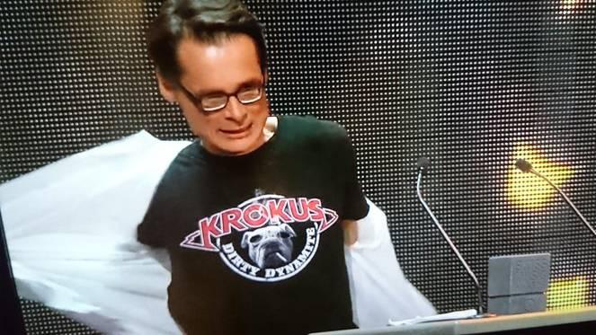 Roger Köppel zieht sein Hemd aus - darunter: Ein T-Shirt der Band Krokus.