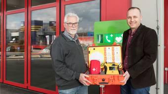 Der erste öffentlich zugängliche Defibrillator: Carrossier Urs Gottesleben (l.), elf Unternehmen und die Gemeinde Neuenhof (im Bild: Gemeindeschreiber Raffaele Briamonte) spannten zusammen, um das Gerät anzuschaffen.