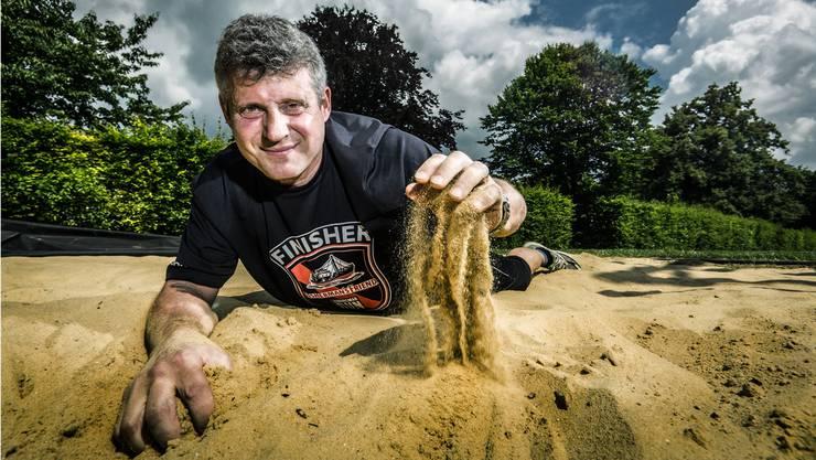 Auf der Sportanlage beim Schulhaus Scheibenschachen in Aarau robbt Andi Jurt vor dem Strongman Run schon mal durch den Sand.