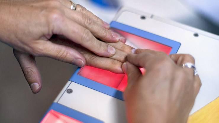 Einem Asylberwerber werden im Empfangs- und Verfahrenszentrums EVZ in Basel Fingerabdrücke genommen.