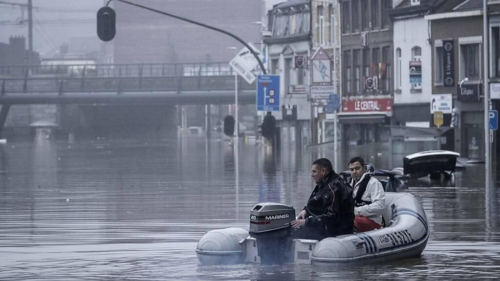 Zwei Männer nutzen ein Gummiboot im Wasser, nachdem die Maas bei schweren Überschwemmungen über die Ufer getreten ist. Foto: Valentin Bianchi/AP/dpa