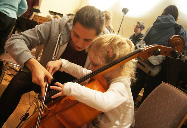 Xenia Burkard erklärt einem Mädchen das Cello