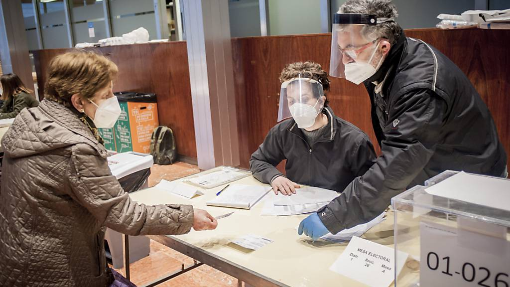 Wahlhelfer kontrollieren unter Beachtung der Corona-Maßnahmen die Dokumente einer Frau, bevor sie ihre Stimme für die katalanischen Regionalwahlen abgibt. Foto: Jordi Boixareu/ZUMA Wire/dpa