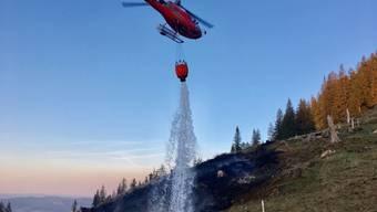 Löschen mit Wasser aus dem Gantrischsee: Ein Helikopter bekämpft den Waldbrand in Blumenstein.