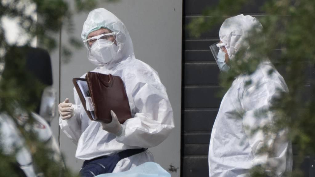 Medizinische Mitarbeiter in Schutzkleidung unterhalten sich, während sie einen Patienten mit Verdacht auf eine Coronavirus-Erkrankung in einem Krankenhaus transportieren. Die russische Hauptstadt Moskau verzeichnet weiterhin Tausende Corona-Neuinfektionen.