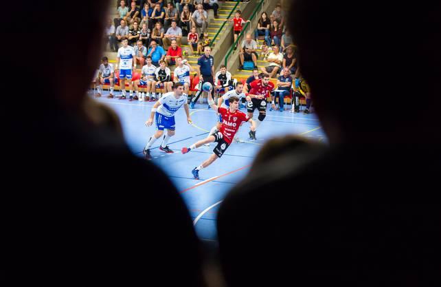 «Der HSC Suhr Aarau lockt schweizweit am meisten Handballfans bei Heimspielen in die Halle. Entsprechend bezeichnet der Verein die Schachenhalle stolz als ‹begeisterndster Handball-Hexenkessel der Schweiz›. Auch beim ersten Heimspiel dieser Saison gegen den HC Kriens-Luzern war die Halle voll. Ich wollte daher unbedingt ein Bild schiessen, das die Action auf dem Spielfeld und die zahlreichen Zuschauer kombiniert.»