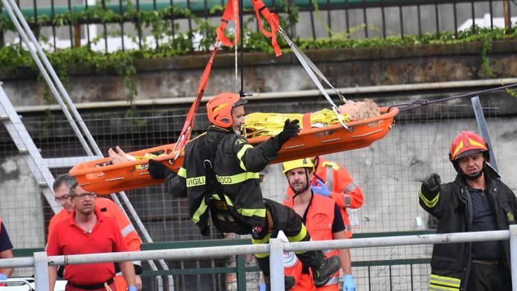 Rettungskräfte bergen nach dem Brückeneinsturz in Genua Verletzte und suchen weiter nach Überlebenden.