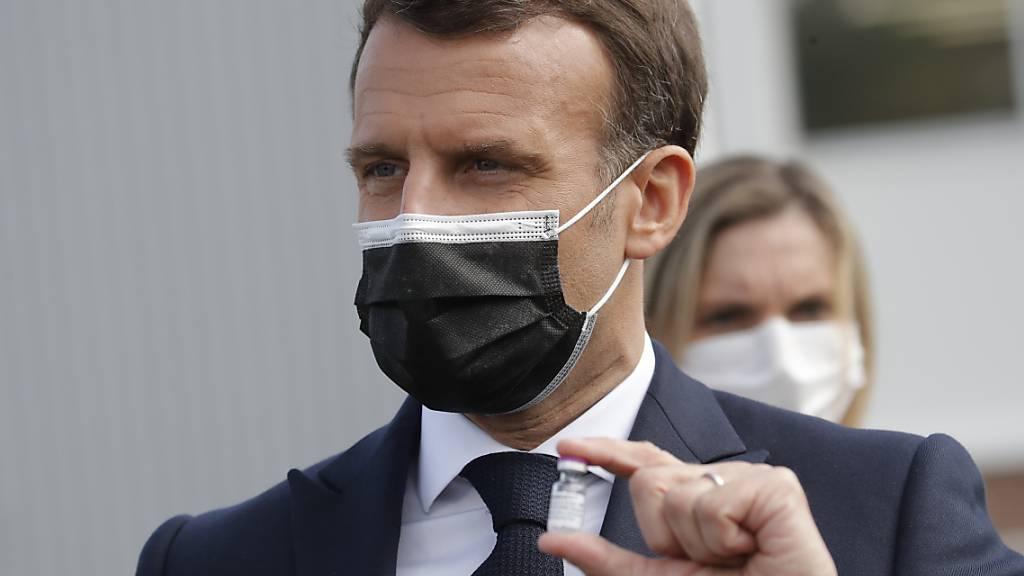 Der französische Präsident Emmanuel Macron hält eine Impfdosis nach einem Besuch in einer Fabrik der Firma Delpharm, die den Corona-Impfstoff von Pfizer/Biontech in Frankreich abfüllt. Foto: Christophe Ena/AP Pool/dpa