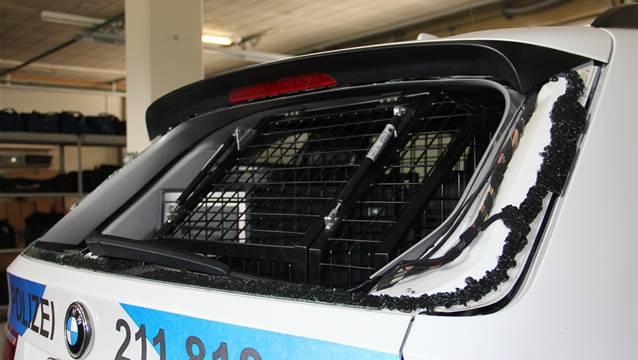 Die Heckscheibe des Polizeifahrzeugs ist zerstört. CM