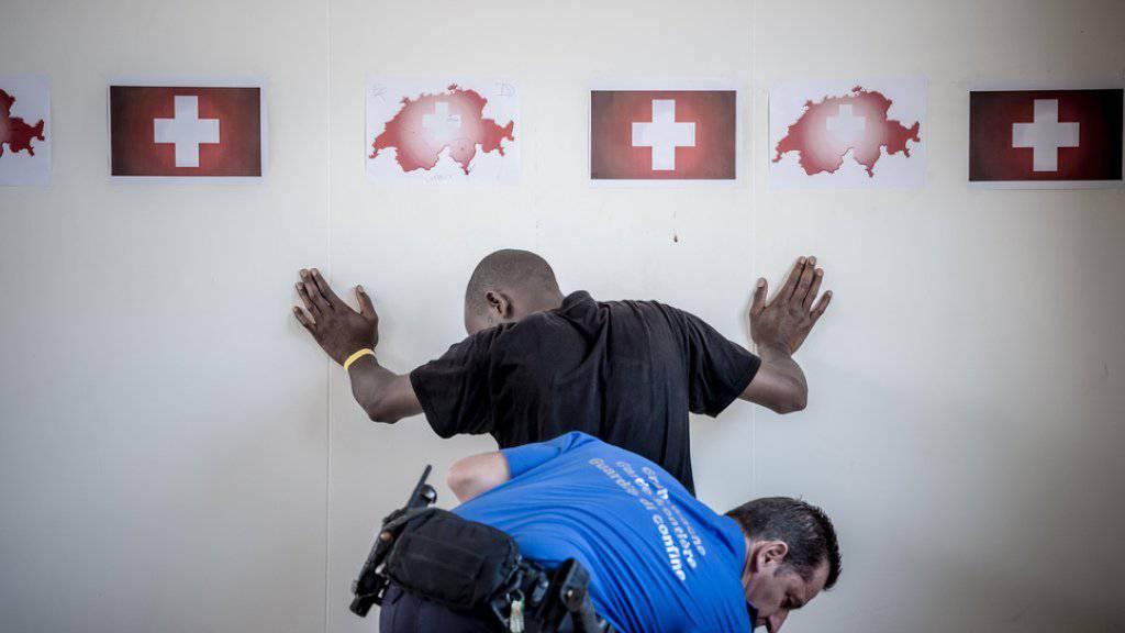 Ein Angehöriger des Grenzwachtkorps durchsucht einen Migranten. (Archiv)
