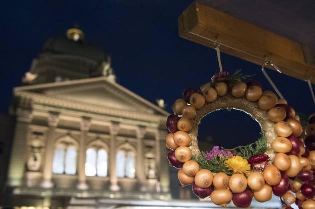 Verschieden farbige Zwiebeln hängen an einem Verkaufsstand vor dem Bundeshaus.