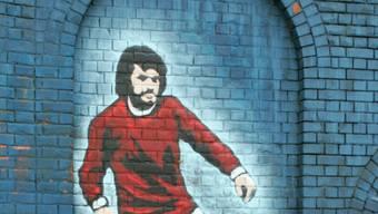 Noch heute heiss geliebt und verehrt: An der Mauer von Belfasts Stadion Windsor Park ist George Best mit einem Wandbild verewigt, vor dem Old Trafford in Manchester mit einer Statue