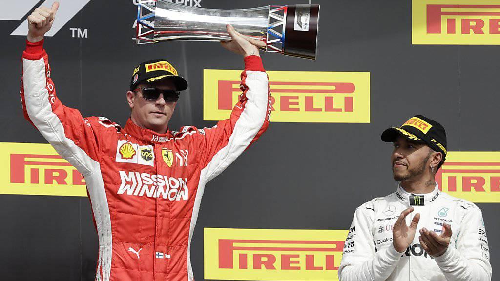 Kimi Räikkönen mit Siegerpokal, Lewis Hamilton applaudiert artig