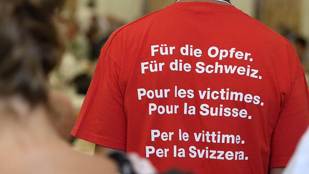 """Ein T-Shirt mit der Aufschrift """"Für die Opfer. Für die Schweiz. Pour les victimes. Pour la Suisse. Per le vittime. Per la Svizzera."""" fotografiert während des grossen Treffens ehemaliger Verdingkindern am Samstag in Mümliswil. (KEYSTONE/Anthony Anex)"""