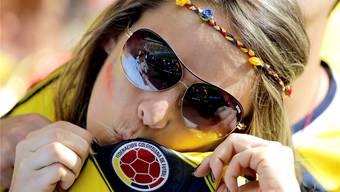 Diese Kolumbianerin freut sich über den Erfolg ihrer Nationalmannschaft - die chinesische Industrie freut sich über den unvorstellbar hohen Absatz von WM-Fanartikeln.